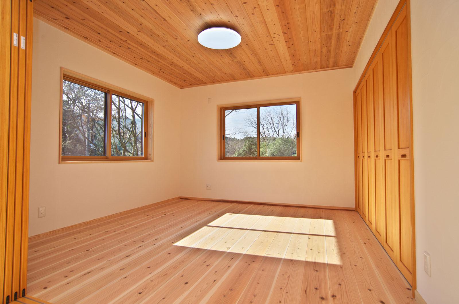一面の漆喰の白さと木の風合いが美しい寝室。